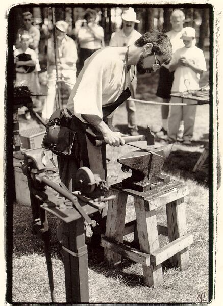 David at                               Orangeville, blacksmithing on double horn                               anvil, in period costume.